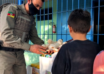 Major Beron ajudando na entrega às crianças em Sapiranga  Fotos: Melissa Costa
