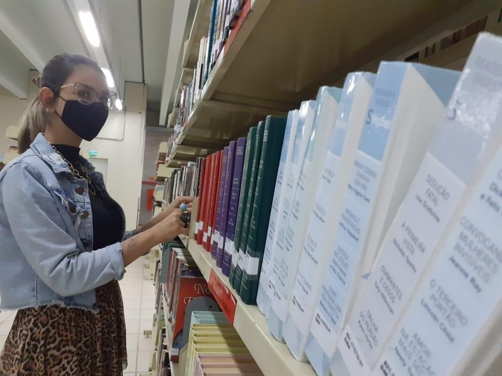 Contista Vitória Duarte Wingert ajuda a organizar os livros físicos  nas prateiras  Foto: Melissa Costa