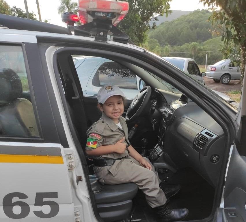 Larissa recebeu uma fardinha completa, com direito a botina e boné, e até posou para a foto na viatura (Foto: Brigada Militar)