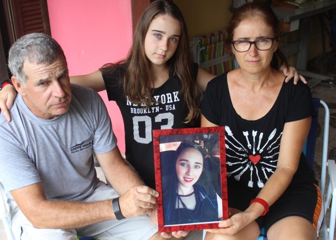 Os pais Paulo e Leopoldina e a irmã Gaziele seguram foto de Gabriele, assassinada em maio do ano passado em Araricá  (Foto: Melissa Costa)