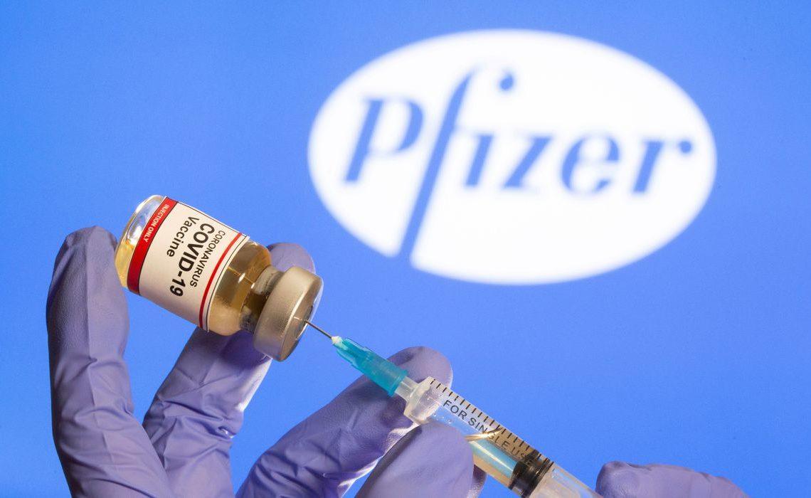 Mulher segura frasco rotulado como de vacina contra Covid-19 em frente a logo da Pfizer em foto de ilustração 30/10/2020 REUTERS/Dado Ruvic