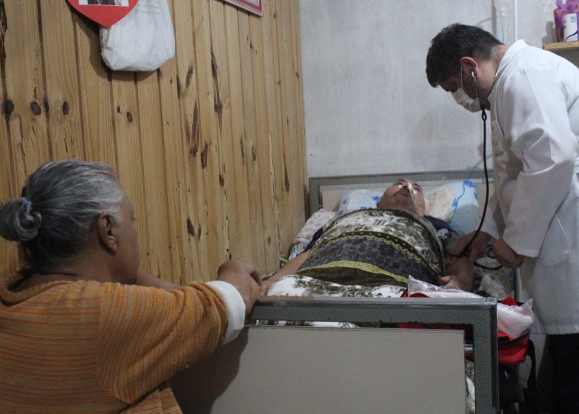 Enfermeiro Fábio  atendendo o paciente Antônio Carlos da Silva, que está acamado,  com o olhar atento da esposa Izaura  (Fotos: Melissa Costa)