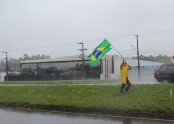 Manifestante enfrenta a chuva na RS-239, em Sapiranga